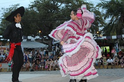 A couple dressed in traditional Mexican costumes dance on stage in the Sayulita plaza